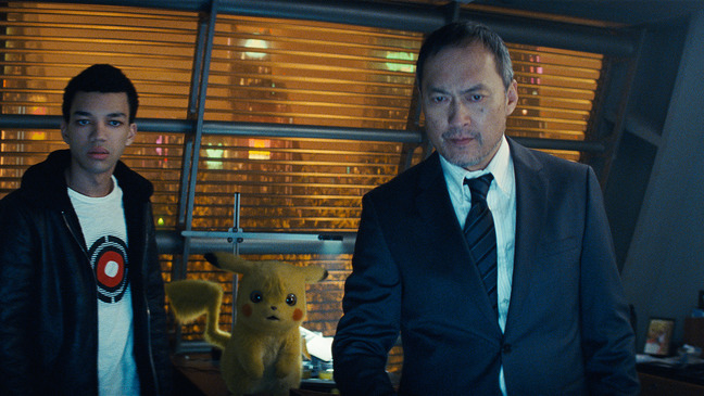 Scene from Detective Pikachu movie with two of the actors and Pikachu in between them.